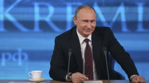 Russian President Vladimir Putin smiles as he takes part in a televised news conference in Moscow