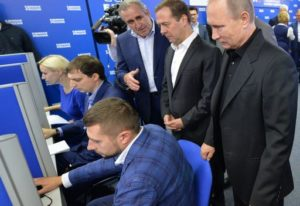 TOPSHOT - Russian President Vladimir Putin (R) and Russian Prime Minister and chairman of the United Russia political party Dmitry Medvedev (2R) visit the party's election campaign headquarters during parliamentary elections in Moscow on September 18, 2016. Russia's ruling party won 49.8 percent of the vote in nationwide legislative elections, partial results showed, as it is set to dominate a new parliament made up of Kremlin loyalists. / AFP PHOTO / SPUTNIK / Alexei Druzhinin