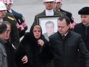 Marina Davydova Karlova,  (C) widow of Russian Ambassador to Turkey Andrei Karlov, stands in front of a picture of her late husband during a ceremonial farewell with full state honours on the tarmac of Ankara's Esenboga Airport in Ankara on December 20, 2016, before the coffin is transported on a Russian plane for Moscow. Veteran diplomat Andrei Karlov was shot nine times in the back by an off-duty Turkish policeman at the opening of an exhibition of Russian photography on December 19, 2016. The brazen killing stunned Ankara and Moscow, which have rowed repeatedly over the Syria conflict but in recent weeks have begun cooperating closely on the evacuations from war-wrecked Aleppo. / AFP PHOTO / ADEM ALTAN